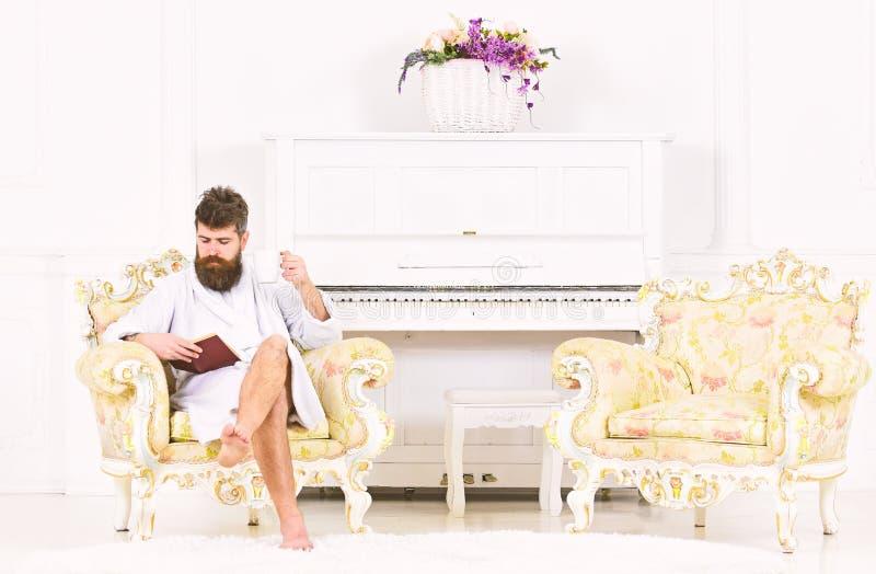 Junger Geschäftsmann, der seinen Morgenkaffee vor Arbeit genießt Starker Kerl, der ein Buch beim Sitzen im Lehnsessel liest lizenzfreie stockbilder