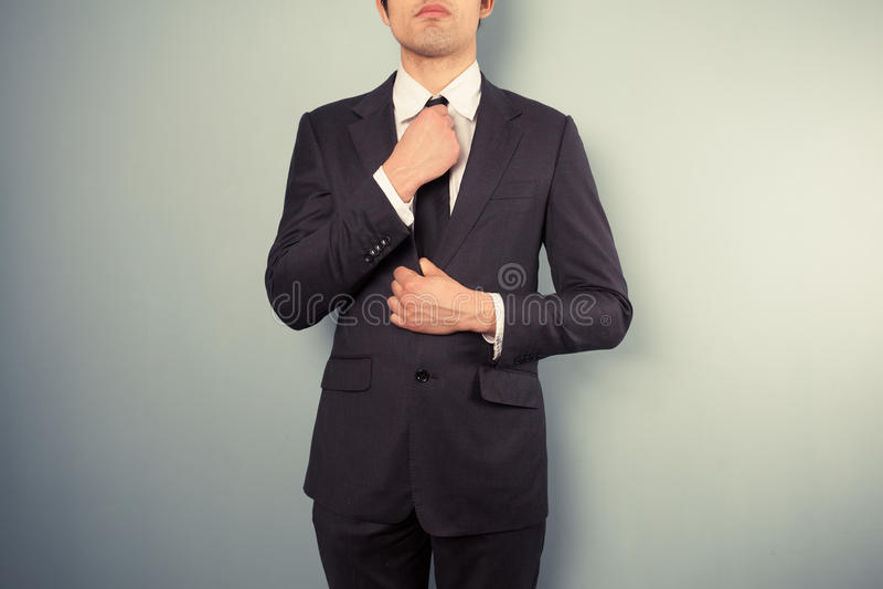 Junger Geschäftsmann, der seins Bindung justiert lizenzfreie stockfotografie