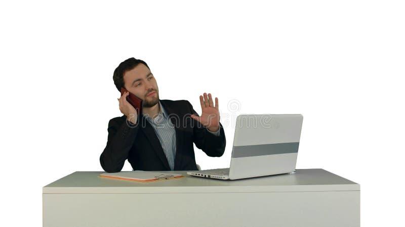 Junger Geschäftsmann, der am Telefon im Büro spricht Auf dem weißen Hintergrund lokalisiert lizenzfreies stockbild