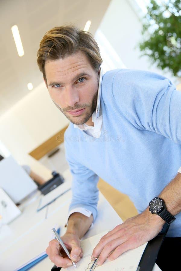 Junger Geschäftsmann, der am Telefon verhandelt lizenzfreie stockfotografie