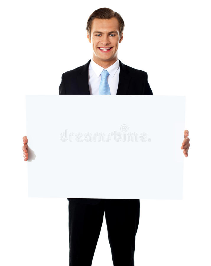 Junger Geschäftsmann, der weiße unbelegte Anschlagtafel anhält lizenzfreie stockbilder