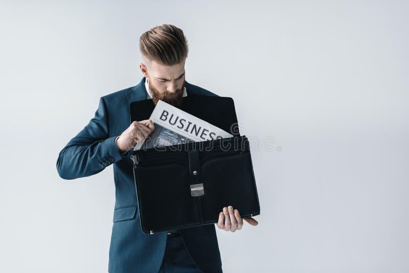 Junger Geschäftsmann, der Zeitung in Aktenkoffer einsetzt lizenzfreie stockfotografie