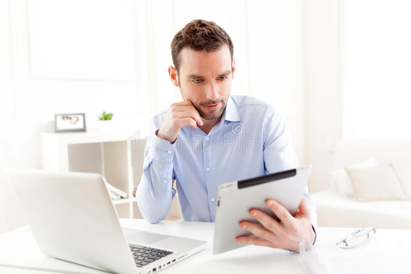 Junger Geschäftsmann, der zu Hause an seiner Tablette arbeitet stockbilder