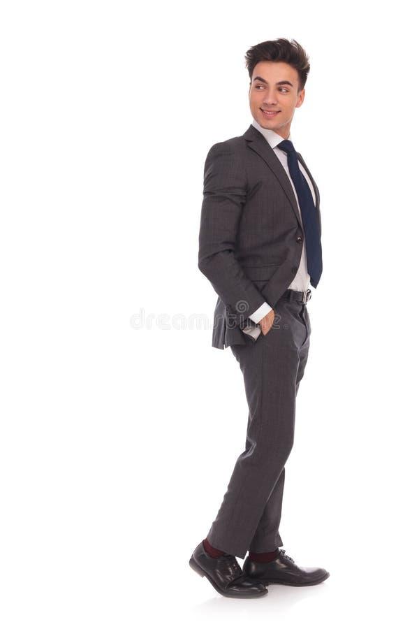 Junger Geschäftsmann, der zurück über seiner Schulter schaut lizenzfreies stockbild