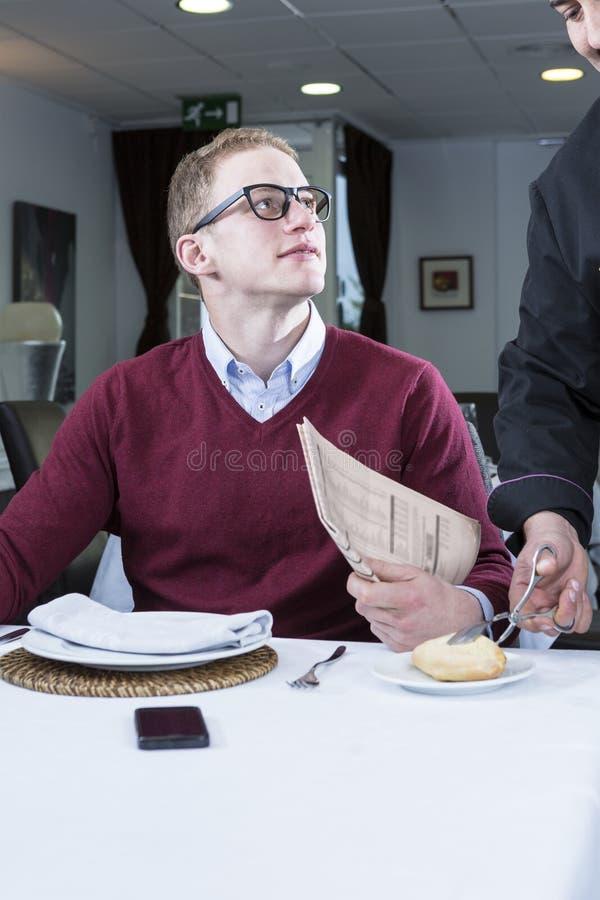 Junger Geschäftsmann an einem Restaurant lizenzfreie stockbilder