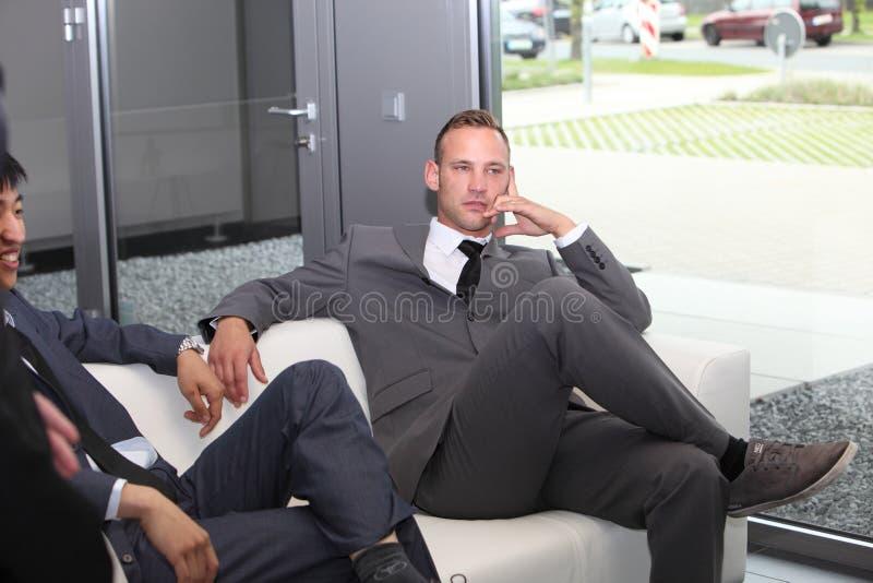 Junger Geschäftsmann in einem Warteraum, der auf dem Sofa sitzt lizenzfreie stockfotos