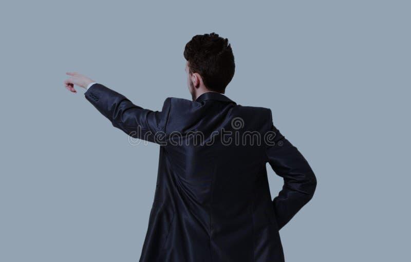 Junger Geschäftsmann in einer Klage zeigend mit seinem Finger stockbild