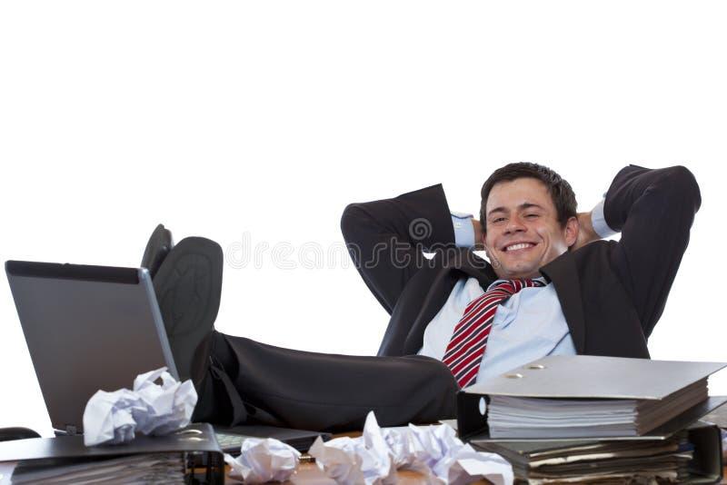 Junger Geschäftsmann entspannt sich mit Füßen am Schreibtisch lizenzfreie stockfotos