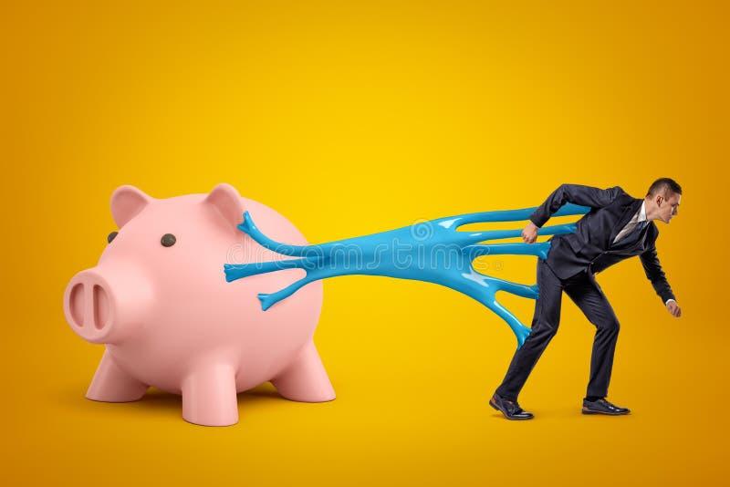 Junger Geschäftsmann gehaftet, um Sparschwein mit blauem klebrigem Schlamm auszuzacken auf gelbem Hintergrund stock abbildung