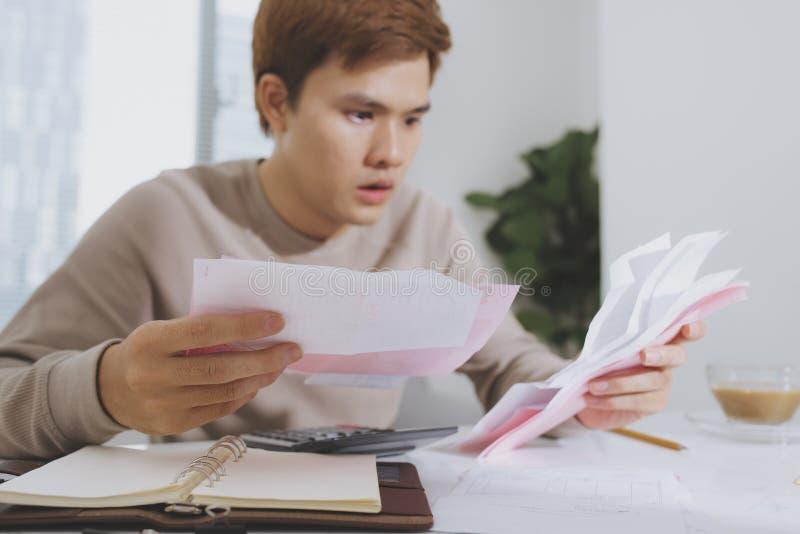 Junger Geschäftsmann gesorgt um Rechnungen lizenzfreies stockbild