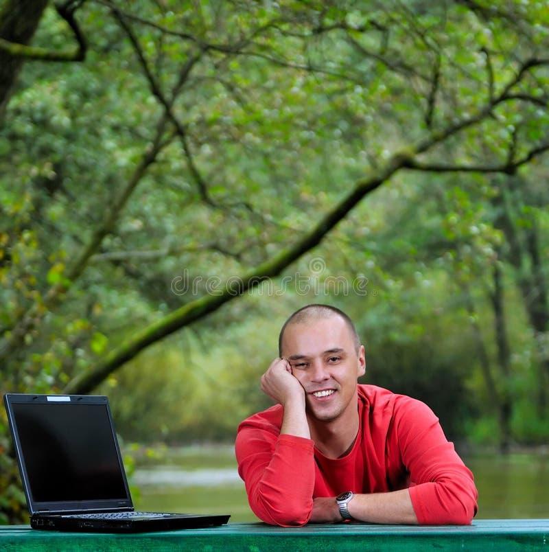 Junger Geschäftsmann im roten Hemd, das an Laptop arbeitet lizenzfreie stockfotos