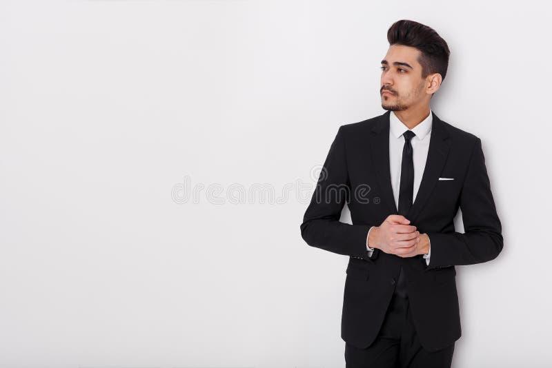 Junger Geschäftsmann im schwarzen Anzug auf einem weißen Hintergrund Überzeugter Mann, der weg von der Kamera schaut lizenzfreie stockfotografie