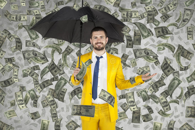 Junger Geschäftsmann ist, Geldregen sehr reich lizenzfreie stockbilder
