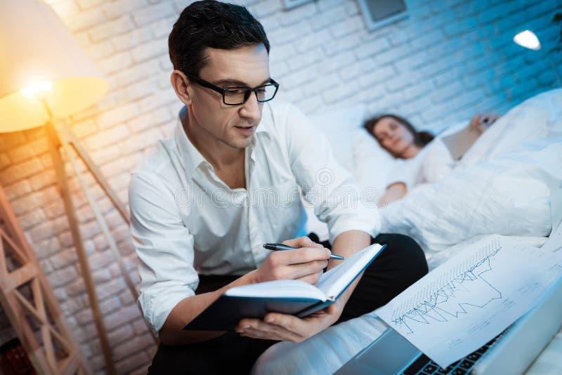 Junger Geschäftsmann macht Anmerkungen im schwarzen Notizblock auf dem Bett Junge Frau schläft nahe bei Mann und hält Buch lizenzfreie stockfotografie