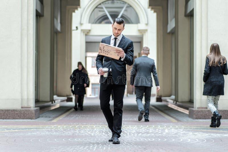 Junger Geschäftsmann mit dem Bart, der weg in der Straße nahe steht stockfotografie