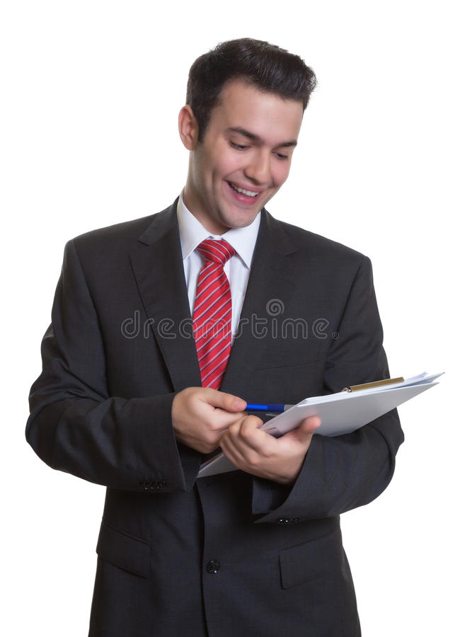 Junger Geschäftsmann mit dem Klemmbrett, das Anmerkungen macht stockfoto