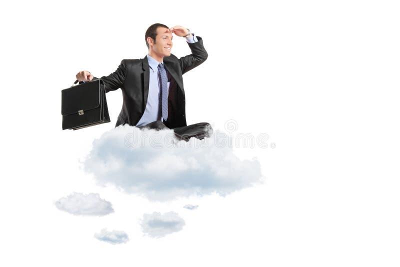 Junger Geschäftsmann mit dem Koffer, der auf einer Wolke sitzt lizenzfreies stockbild