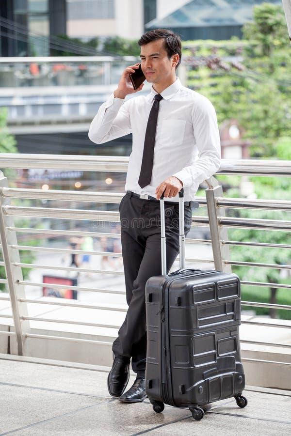 Junger Geschäftsmann mit dem Unterhaltungshandy des Gesellschaftsanzugs im Freien mit Gepäck auf Geschäftsreisereise stockfotografie
