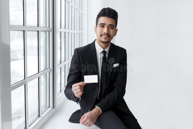 Junger Geschäftsmann mit leerer Visitenkarte in der Hand lizenzfreies stockbild