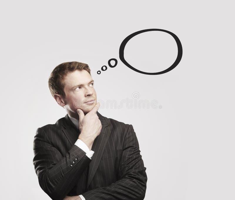 Junger Geschäftsmann mit Spracheluftblasen nach innen. lizenzfreies stockbild