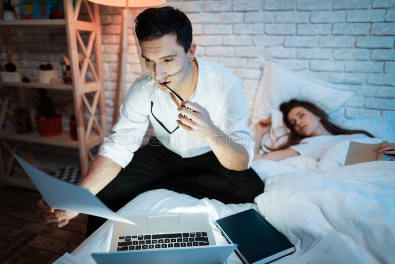 Junger Geschäftsmann studiert Grafiken auf Laptop Auf Bett sind Blätter mit Diagrammen lizenzfreies stockfoto