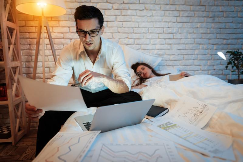 Junger Geschäftsmann studiert Grafiken auf Laptop Blätter werden über Bett zerstreut lizenzfreie stockfotos