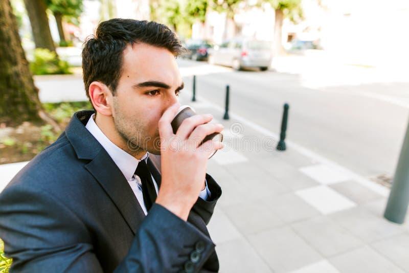 Junger Geschäftsmann trinkt Kaffee zum Mitnehmen stockfotos