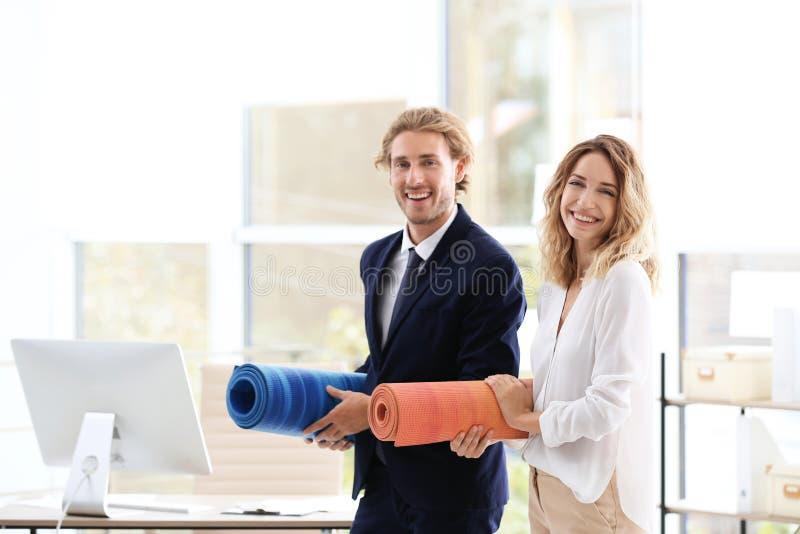 Junger Geschäftsmann und Geschäftsfrau, die Yogamatten im Büro hält stockbilder