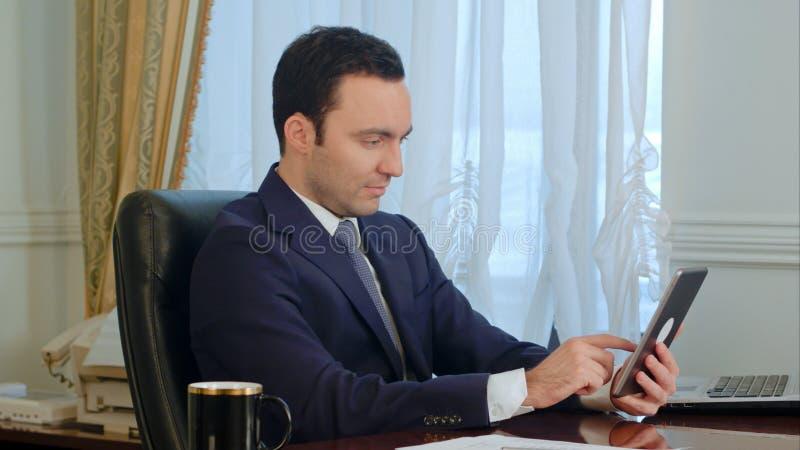 Junger Geschäftsmann unter Verwendung der modernen digitalen Tablette, die das Internet sucht lizenzfreies stockfoto