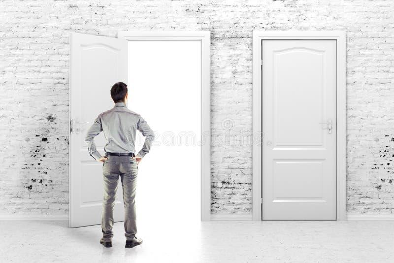 Junger Geschäftsmann vor einer offenen Tür lizenzfreie stockfotos