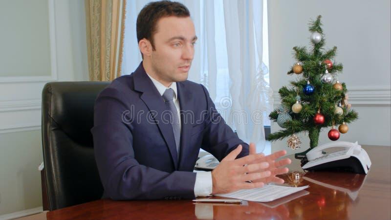 Junger Geschäftsmann, welche guten Nachrichten beim Sitzen durch Tabelle im Büro sagt stockfotografie