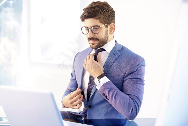 Junger Geschäftsmannbindungsknoten stockfotos