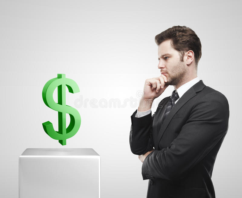 Junger Geschäftsmannblick auf die grünen US-Dollar Sig lizenzfreie stockbilder