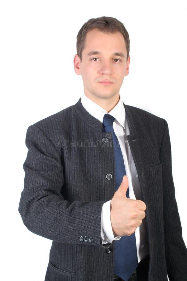 Junger Geschäftsmannerscheinendaumen oben lizenzfreies stockfoto