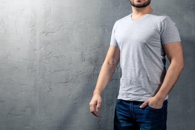 Junger gesunder Mann mit grauem T-Shirt auf konkretem Hintergrund mit copyspace für Ihren Text stockfotografie