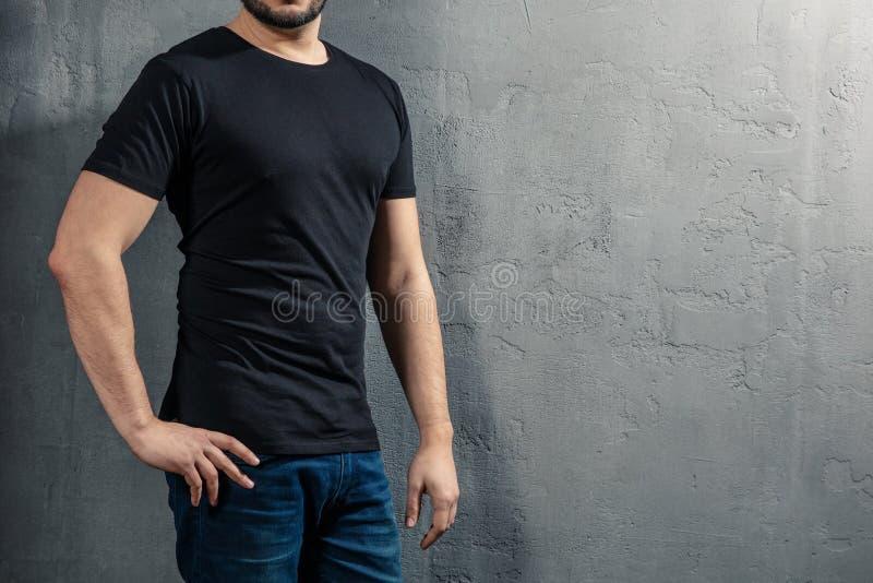 Junger gesunder Mann mit schwarzem T-Shirt auf konkretem Hintergrund mit copyspace für Ihren Text lizenzfreie stockbilder