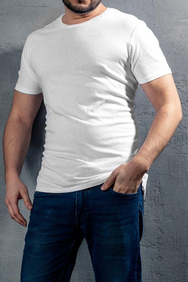 Junger gesunder Mann mit weißem T-Shirt auf konkretem Hintergrund lizenzfreies stockfoto