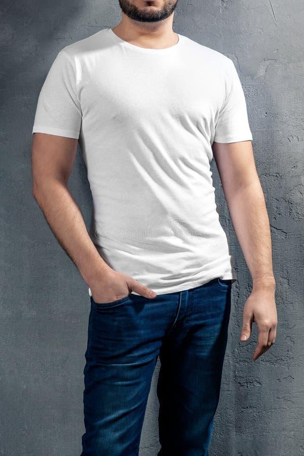 Junger gesunder Mann mit weißem T-Shirt auf konkretem Hintergrund lizenzfreie stockfotografie