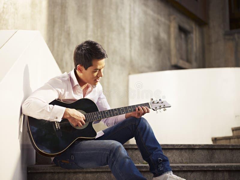Junger Gitarre spielender und singender Mann stockbilder