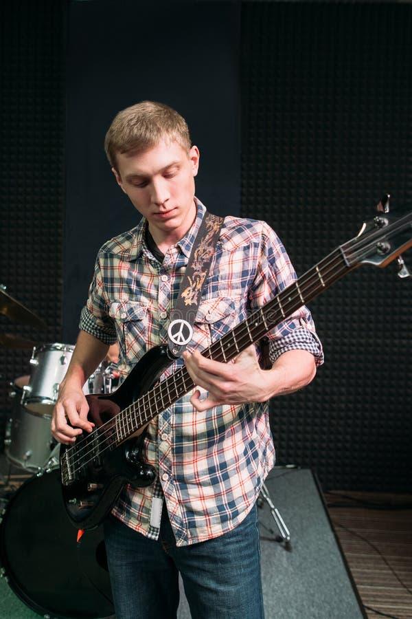 Junger Gitarrist, der Musik im Studio spielt lizenzfreie stockfotografie