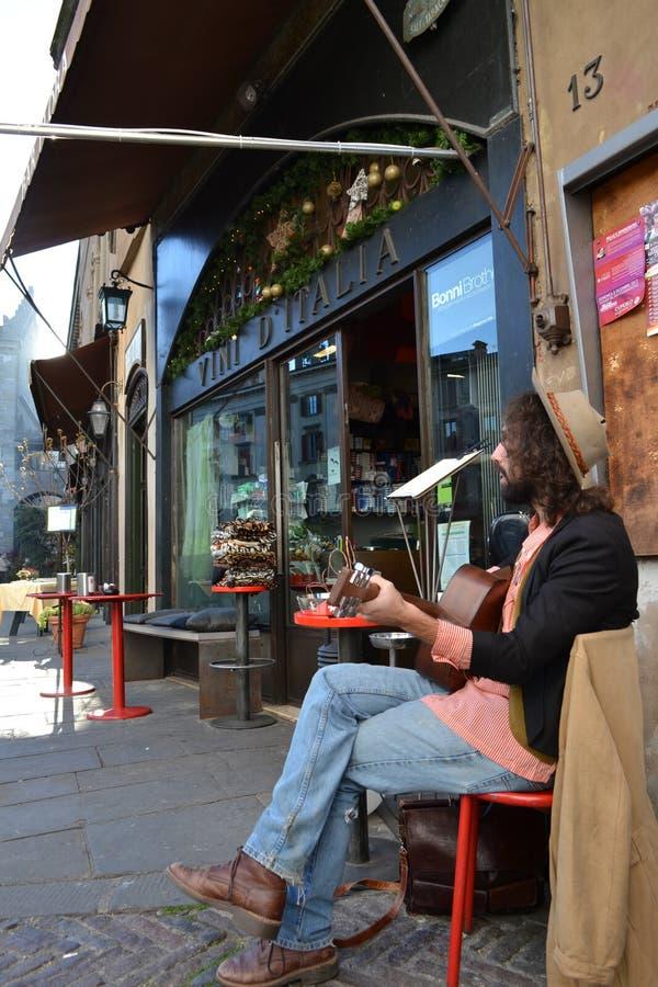 Junger Gitarrist, der seine Gitarre spielt und Sitzen nahe Weinbar singt lizenzfreie stockfotos