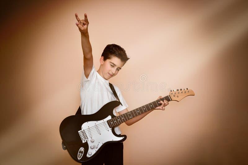 Junger Gitarrist mit der Hand, die sich Zeichen von Hörnern zeigt lizenzfreie stockfotografie