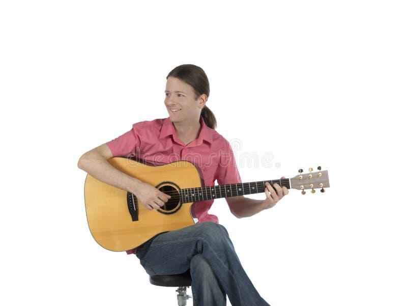 Junger Gitarrist mit einem Lächeln, das seine Gitarre spielt stockfoto