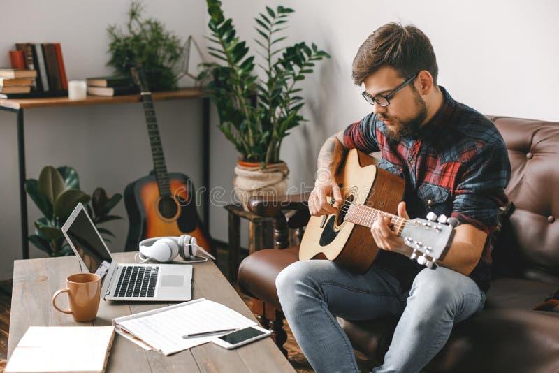 Junger Gitarristhippie zu Hause, der die Gitarre betrachtet Anmerkungen hält stockfotos
