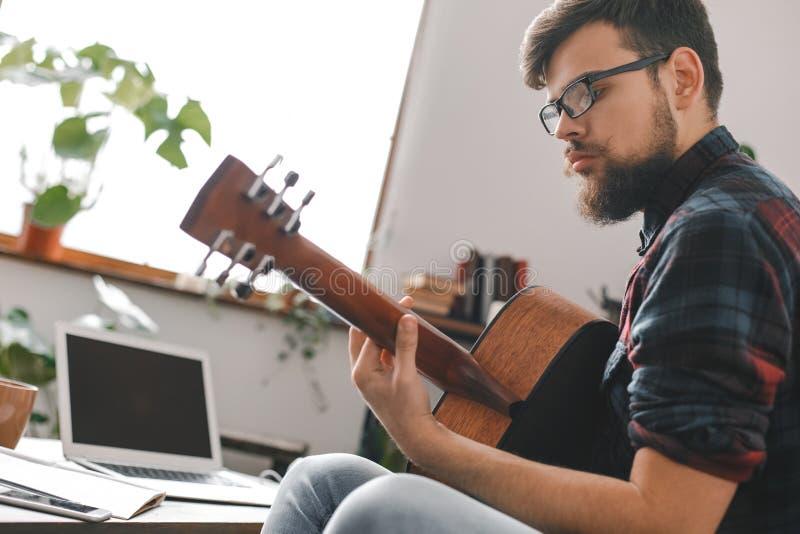 Junger Gitarristhippie zu Hause, der Gitarrenfensterlicht hält lizenzfreie stockfotos