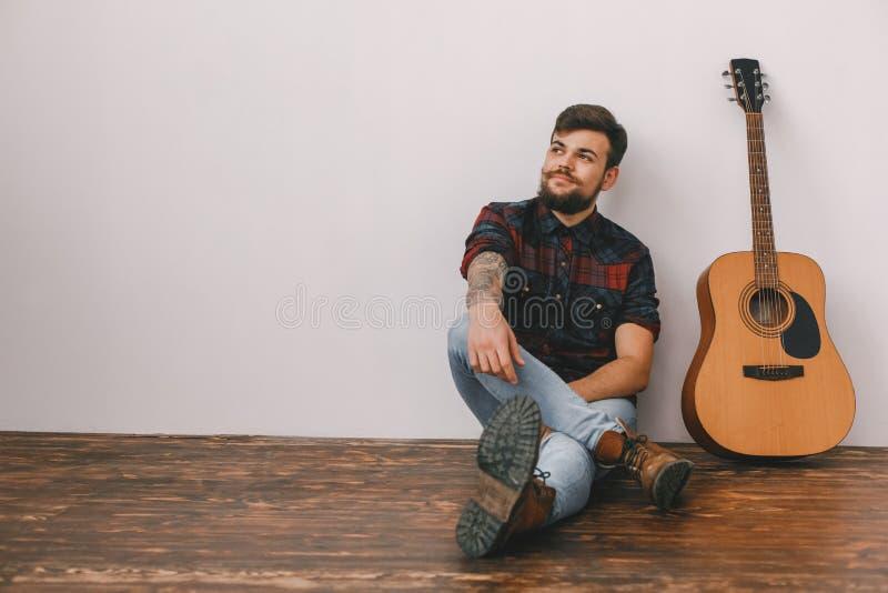 Junger Gitarristhippie zu Hause mit dem Gitarrensitzen durchdacht lizenzfreies stockfoto