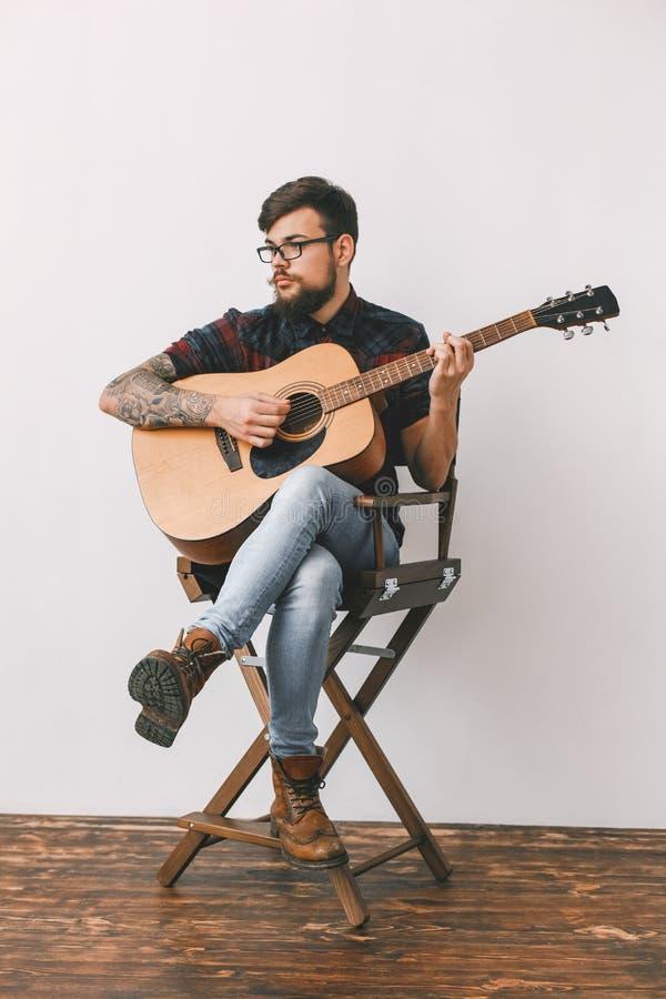 Junger Gitarristhippie zu Hause mit Gitarre auf dem Stuhlvollkörperporträt lizenzfreies stockbild