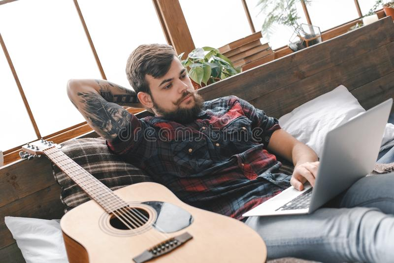 Junger Gitarristhippie zu Hause mit Gitarre im Schlafzimmergraseninternet lizenzfreie stockfotografie
