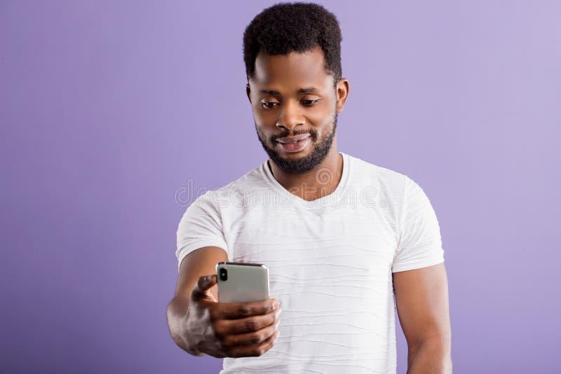 Junger glücklicher afrikanischer Mann mit dem Mobiltelefon lokalisiert auf lila Hintergrund stockfotos