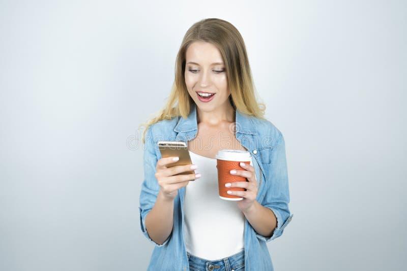 Junger glücklicher blonder Frauenholding Smartphone in einer Hand und in Tasse Kaffee in einem anderen lokalisierten weißen Hinte lizenzfreies stockfoto